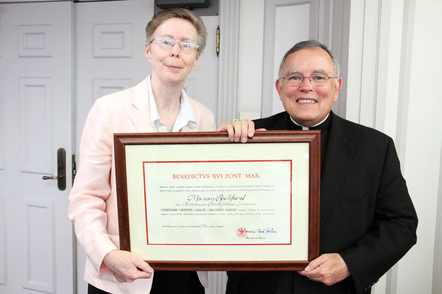 Mary Rochford (left) receives the official documentation upon being named a Dame of the pontifical Order of St. Gregory the Great from Archbishop Charles Chaput Sept. 6 at the Archdiocesan Pastoral Center in Philadelphia. (Sarah Webb)