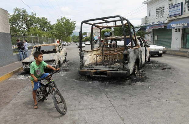 A child rides his bike past two burned vehicles Aug. 12 after five people were killed in gang-related attacks in Nueva Italia, Mexico. About 28 percent of the approximately 100,000 people murdered in Latin America and the Caribbean every year are between ages 10 and 19, according to U.N. figures.(CNS photo/Leovigildo Gonzalez, Reuters)