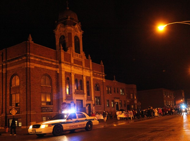 "A police car leads members of various parishes from St. Mary Magdalene Church to Our Lady of Guadalupe Church in Chicago during a ""Pilgrimage for Peace"" in mid-October. The marchers stopped to pray at some of the places where youth and adults have been killed in gun and other violence over the last year. (CNS photo/Karen Callaway, Catholic New World)"