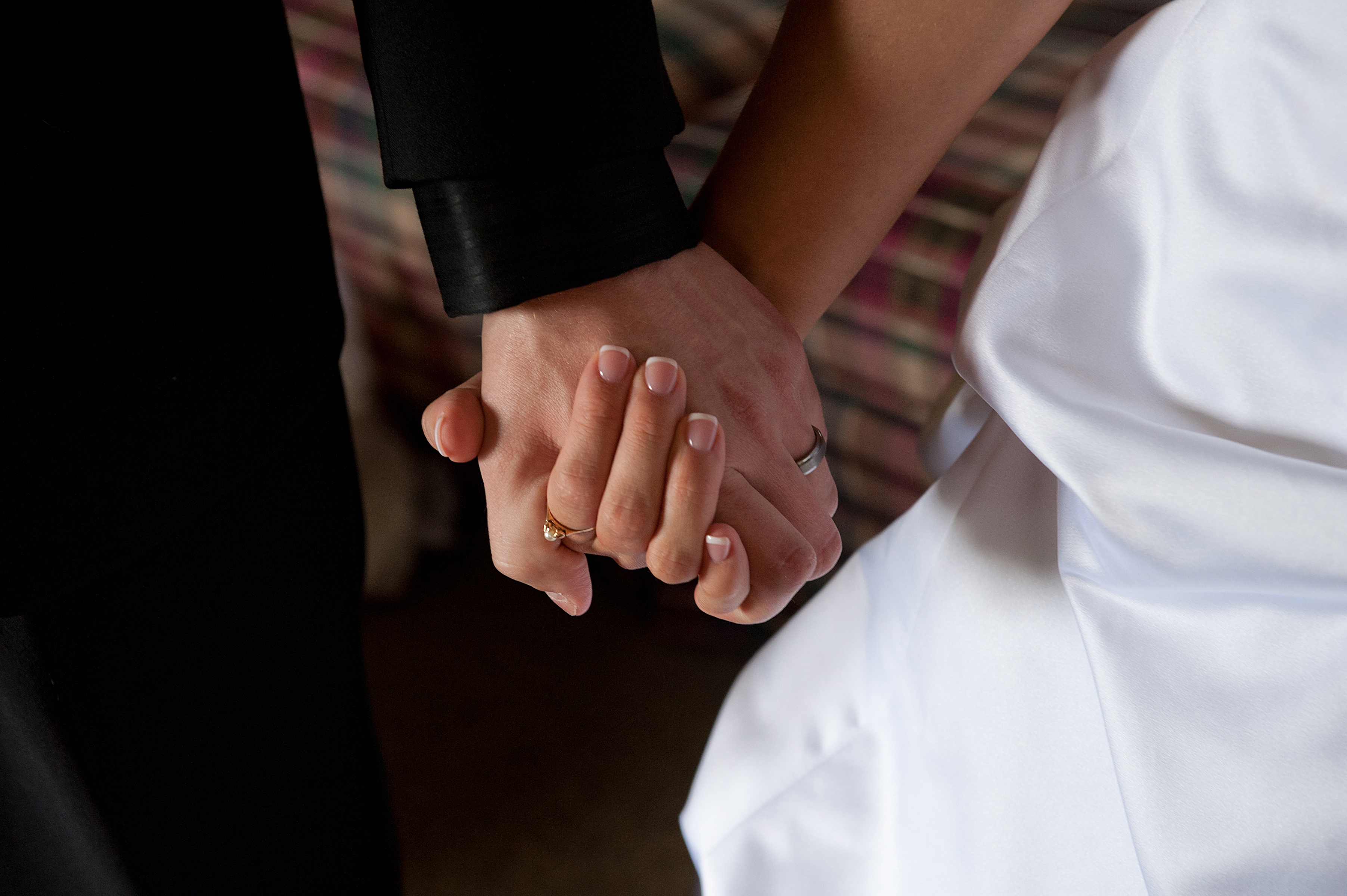 GROOM, BRIDE HOLD HANDS ON THEIR WEDDING DAY