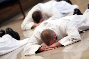 Robert Gross and David Waters Jr. lay prostrate in prayer during their ordination.