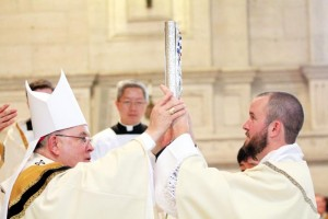 "Archbishop Charles Chaput places the Book of the Gospels in the hands of Robert Gross and says, ""receive the Gospel of Christ, whose herald you now are. Believe what you read, teach what you believe, and practice what you teach."""