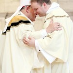 Deacon Charles Ravert shares a kiss of peace with Archbishop Chaput during the ordination.