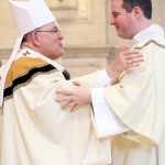 Archbishop Charles Chaput offers a kiss of peace to the newly ordained deacon, David Waters Jr.