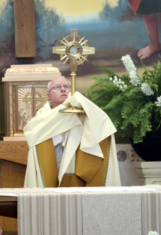 Msgr. Joseph Prior, pastor of St. John the Evangelist, blesses during benediction that end the procession at St. John the Evangelist Parish in Lower Makefield.