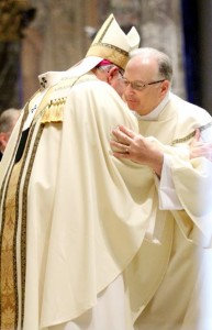 Archbishop Charles Chaput offers a kiss of peace to the newly ordained deacon, Louis Quaglia.