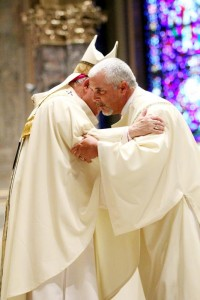 Deacon Patrick Kelly shares a kiss of peace with Archbishop Chaput during the ordination.