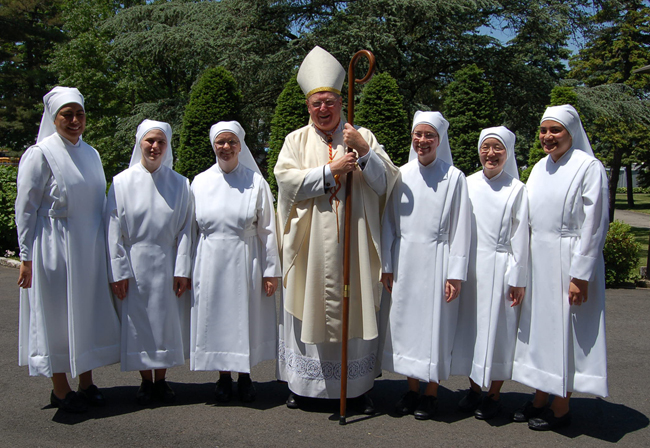 New York Cardinal Timothy Dolan stands with sisters who made their first vows June 1 with the Little Sisters of the Poor, an order of religious women that runs a nursing home in Philadelphia.