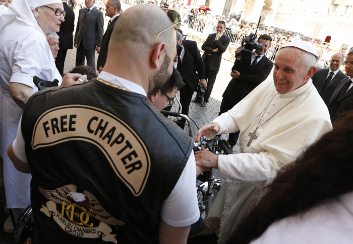Pope Francis greets a Harley-Davidson biker as he meets with pilgrims who have  disabilities following Mass in St. Peter's Square at the Vatican June 16. The Year of Faith Mass concluded a weekend of events calling attention to care for the aged, the sick, the unborn and those with disabilities. (CNS photo/Paul Haring)