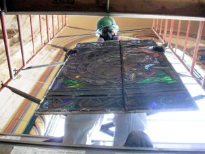 A worker from Beyer Studio, in Germantown, removes a panel of a stained glass window from Ascension Church.