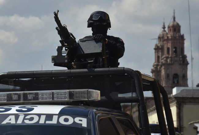 A federal police officer mans a weapon atop a vehicle in the Mexican state of Michoacan Oct. 28. Some at St. James the Apostle Parish in a rural pocket of Michoacan formed self-defense groups earlier this year to protect themselves from extortion attempts and attacks by organized criminal groups. (CNS photo/Alan Ortega, Reuters)