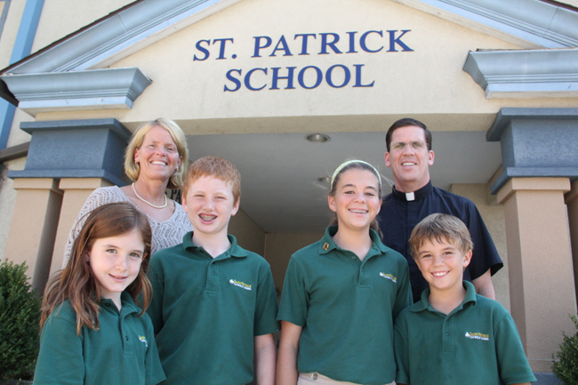 Patti O'Donnell (back left), principal of St. Patrick School in Malvern and Father Christopher Redcay (right), parish pastor, stand with students of the school that was named a National Blue Ribbon School, along with St. Andrew School in Newtown. (Photos by Sarah Webb)