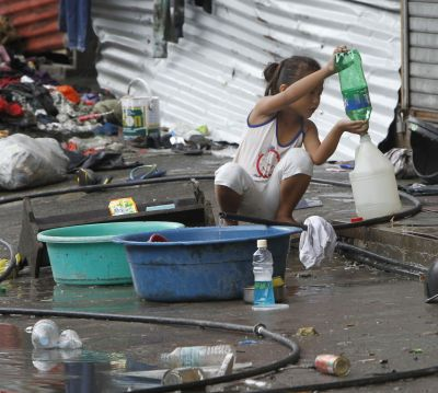 A girl transfers drinking water she collected from a faucet Nov. 12 after Super Typhoon Haiyan devastated Tacloban, Philippines. (CNS photo/Romeo Ranoco, Reuters)