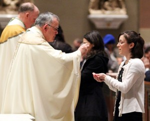 Renee Casani, who accepted the St. John Neumann Award for five years' service, receives Communion from Archbishop Chaput during the Mass.