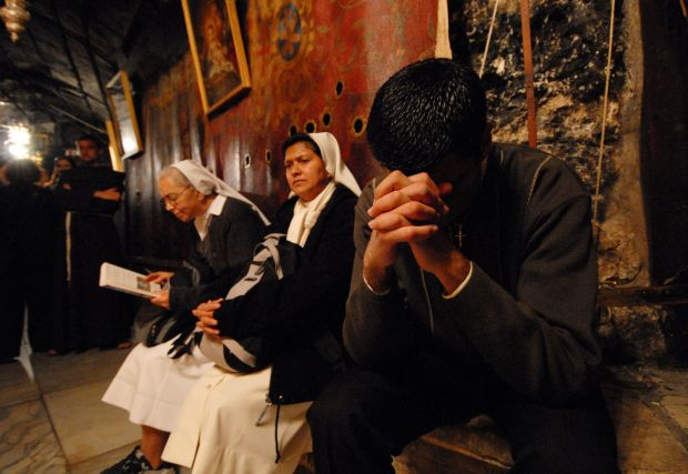 A Palestinian Christian prays in the grotto of the Church of the Nativity in the West Bank town of Bethlehem on Christmas Eve. (CNS photo/Debbie Hill)