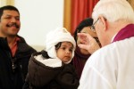 Little Alinah Roy, held by her mother Rani, receives ashes from Father Bonner as her dad Roy Thomas looks on.