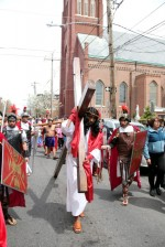 Jesus (Jose Miguel Almaras) carries his cross on the street past Annunciation Church.