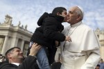 A child gives Pope Francis a kiss as the pontiff arrives to lead his general audience in St. Peter's Square at the Vatican April 2. (CNS photo/Alessandro Bianchi, Reuters)