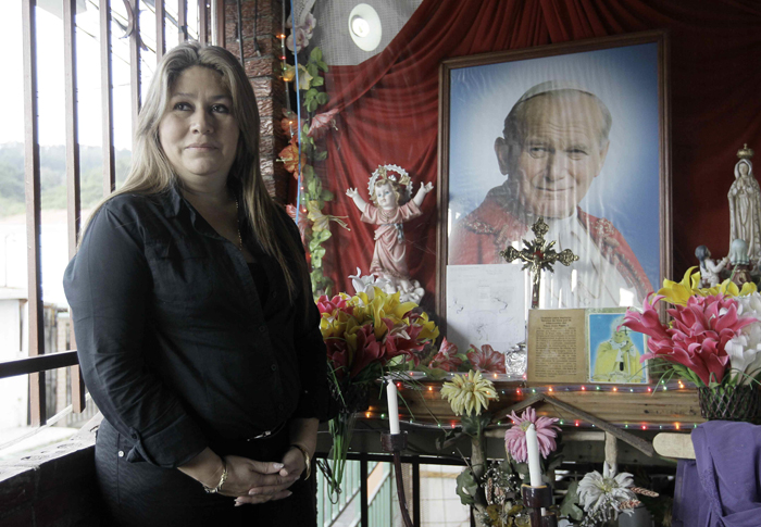 Floribeth Mora Diaz listens to the questions from reporters in front of a shrine to Blessed John Paul II at her home in Dulce Nombre de Tres Rios, Costa Rica, in this July 5, 2013, file photo. Mora said she said she was cured through the intercession of Blessed John Paul II after suffering an aneurysm in April 2011. Her cure was the second miracle in the sainthood cause of the late pontiff, who will be canonized April 27 at the Vatican. (CNS photo/Jeffrey Arguedas, EPA)