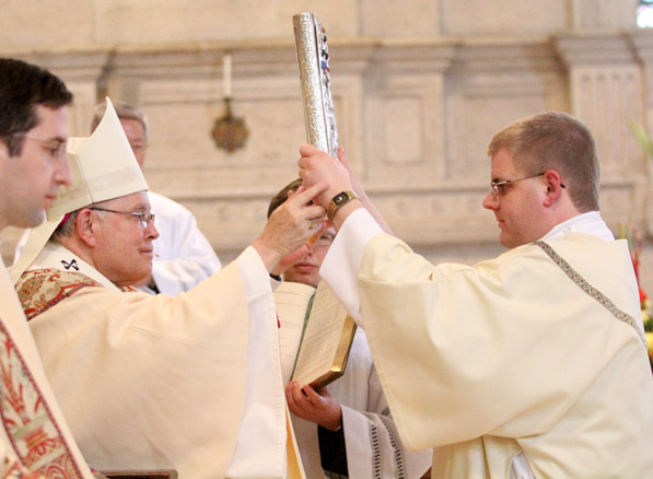 Rev. Mr. Steven Kiernan receives the Book of Gospels from Archbishop Charles Chaput during the rite of ordination as a deacon in May 2014.