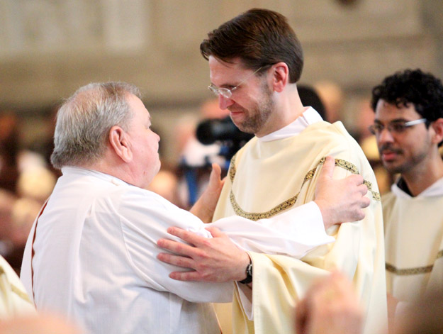 During his ordination as a transitional deacon in 2014, Rev. Mr. Joseph Zaleski receives a fraternal kiss from his father, Permanent Deacon Stanley Zaleski, who also preached the homily for his son's first Mass this year. (Sarah Webb)