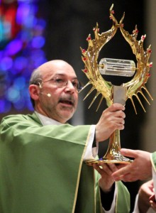 Father Angelo Hernandez, parochial vicar at the Cathedral Basilica of SS. Peter and Paul, blesses the people with the relic of St. John Paul II at the end of Mass July 19.