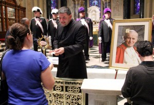 Father Gregory Gresko from the St. John Paul II National Shrine in Washington, D.C., gives out prayer cards that were touched to the relic.