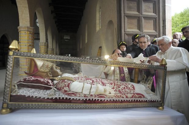 Pope Benedict XVI places a white stole on the remains of St. Celestine V, a 13th-century pope, during his 2009 visit to the earthquake-damaged Basilica of Santa Maria di Collemaggio in L'Aquila, Italy.  (CNS photo/L'Osservatore Romano via Reuters)