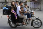 A Palestinian family rides a motorcycle as they flee their house in Khan Younis, Gaza Strip, Aug. 1. (CNS photo/Ibraheem Abu Mustafa, Reuters)
