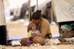 A woman who fled the violence in the Iraqi town of Sinjar sits with a child inside a tent at a camp in Syria's northern town of Qamishli Aug. 17. (CNS photo/Rodi Said, Reuters)