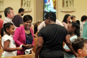 New student Jillian Sweat and her mother Barbara are greeted by Shania Spivey and her mother Veronica before the prayer service.