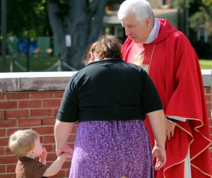 Father Rymdeika greets Jennifer Hoban and her son Lucas after Mass.