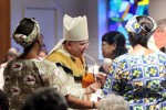 Archbishop Charles Chaput accepts the offertory gifts (from left ) from Medical Mission Sisters Therese Tindirugamu, Edith Dug-Yi and Emma Panizales. (Sarah Webb)