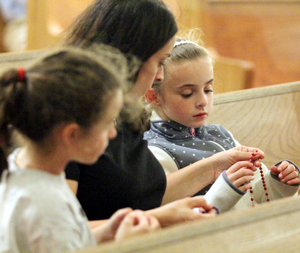 Sara Martin helps her daughters Natalie (left) and Addison pray the rosary Oct. 28 at St. Christopher Church, Philadelphia. (Sarah Webb)