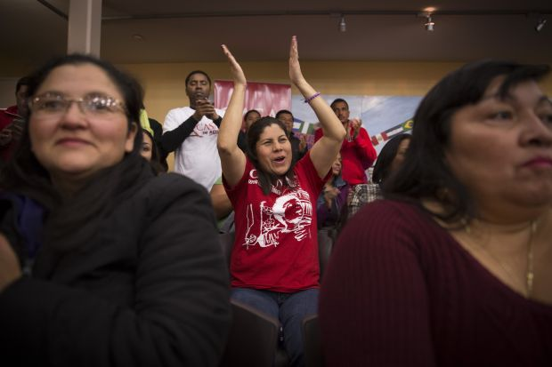 A woman at CASA de Maryland's Multicultural Center in Hyattsville, Md., applauds Nov. 20 after hearing President Barack Obama's national address on immigration. The president extended deferral of deportations to parents of millions of U.S. citizens and legal residents. (CNS photo/Tyler Orsburn)