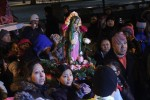 Children carry a statue of the Blessed Mother in procession.