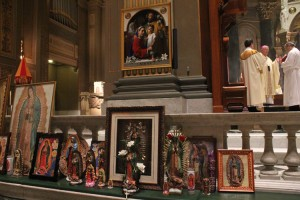 Images of Our Lady of Guadalupe brought by people attending the Mass line the altar rail of the cathedral as Archbishop Chaput prays the collect prayer during Mass.