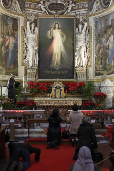 People pray before the Eucharist and an image of Jesus of Divine Mercy at Santo Spirito Church in Rome in this Jan. 14, 2011 file photo. (CNS photo/Paul Haring)