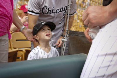 A young fan looks up to Tyler Flowers of the Chicago White Sox as the catcher signs baseballs during spring training March 11 at Camelback Ranch ballpark in Glendale, Arizona. (CNS photo/Nancy Wiechec)