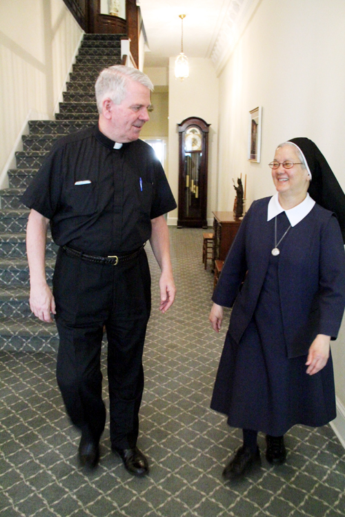 Father Paul Kennedy, pastor of St. Katherine Parish, talks with Sister Mary Praxedes in the parish rectory. (Sarah Webb)