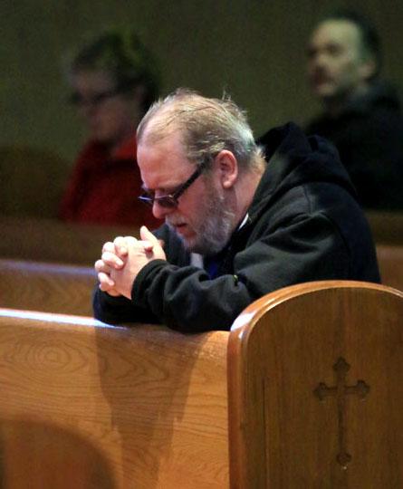 Rick Mullen prays before mass