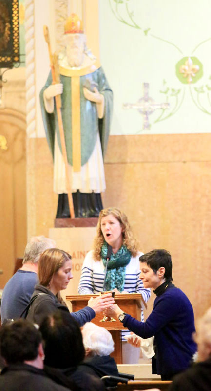 Eucharistic Minister Diana DeMatteo, cantor Marie Herbert
