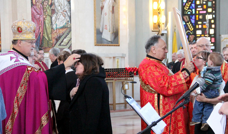 After venerating the relic, people are anointed with holy oil by Archbishop Soroka and priests at the service.