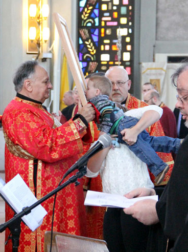 A young boy is lifted to venerate the relic.