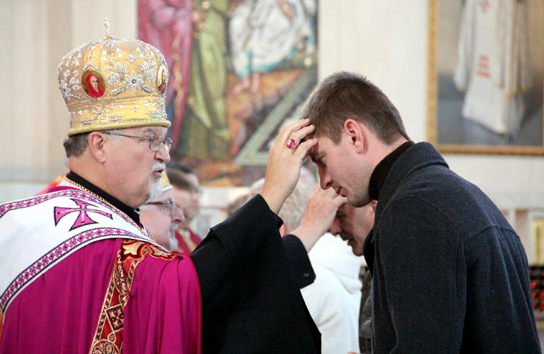 Archbishop Soroka anoints a young man with oil.