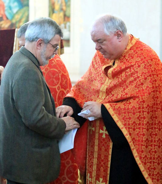 Msgr. Peter Waslo annoints a man's hands with holy oil.