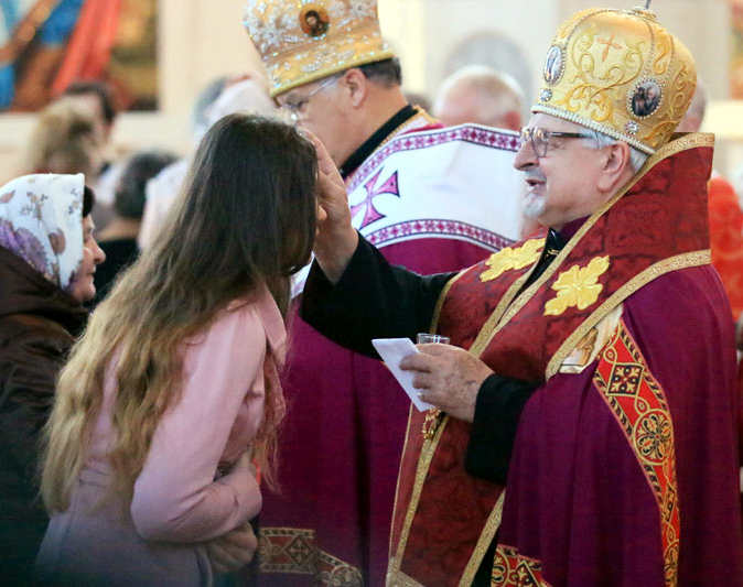 Bishop John Bura, auxillary bishop, annoints a young woman.