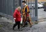 A homeless woman walks past a Swiss guard as she enters the Vatican March 26. While enjoying a private visit to the Sistine Chapel, homeless people were surprised by a visit from Pope Francis. (CNS photo/Max Rossi, Reuters)