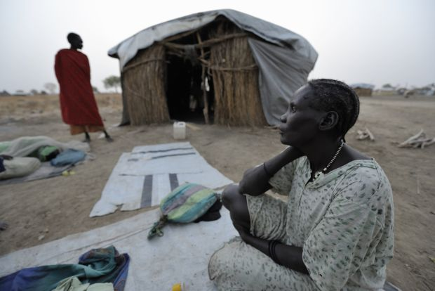 A displaced woman awakens in the morning after sleeping outside on the ground in 2013 in front of shelter in Agok, in the contested Abyei region along the Sudan-South Sudan border. (CNS photo/Paul Jeffrey)