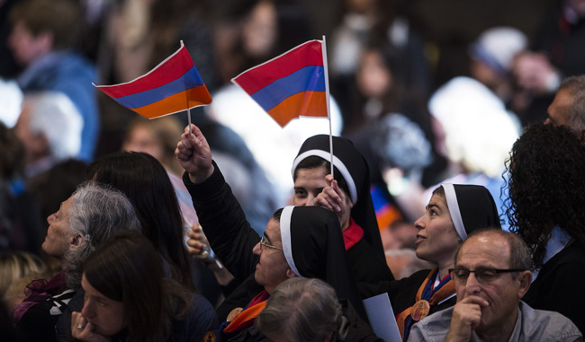 Nuns wave the Armenian flag during an April 12 Mass celebrated by Pope Francis in St. Peter's Basilica at the Vatican to mark the 100th anniversary of the Armenian genocide. (CNS photo/Cristian Gennari)